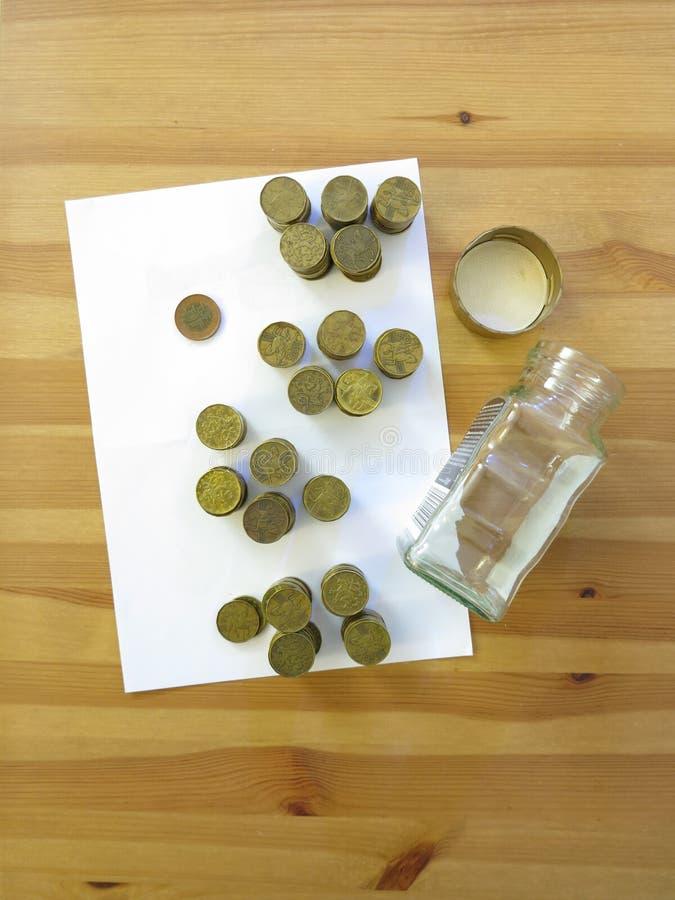 Mynt från exponeringsglassparbössan på taben royaltyfria foton
