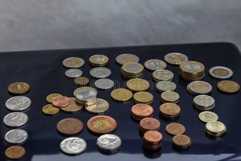 Mynt från olika länder läggas ut på buntar royaltyfria bilder