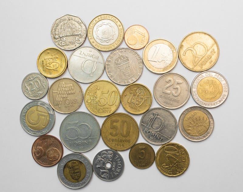 Mynt från olika länder på vit royaltyfri bild