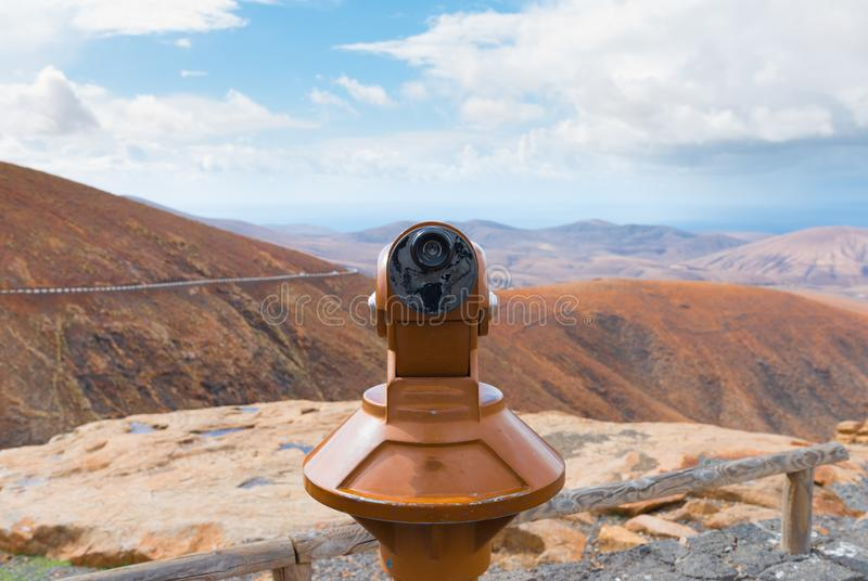 Mynt-fungeringsbinokulärt på scenisk utpost med bergskedja och himmel i bakgrund arkivfoton