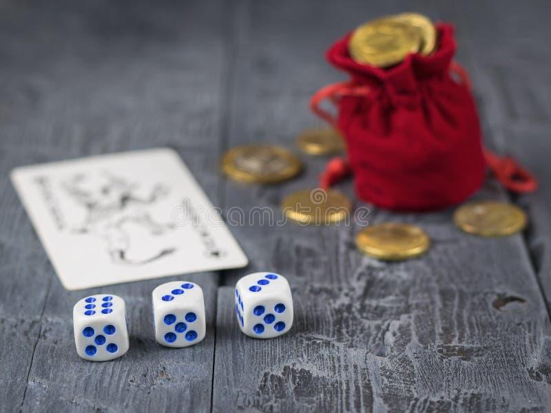 Mynt hällde från en påse och en röd tärning på en trämörk tabell royaltyfri fotografi