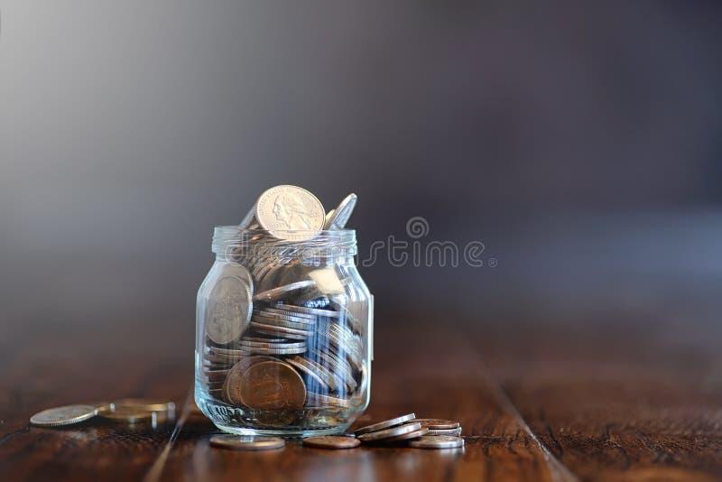 Mynt i en glass krus på ett trägolv Fick- besparingar från mynt arkivbilder