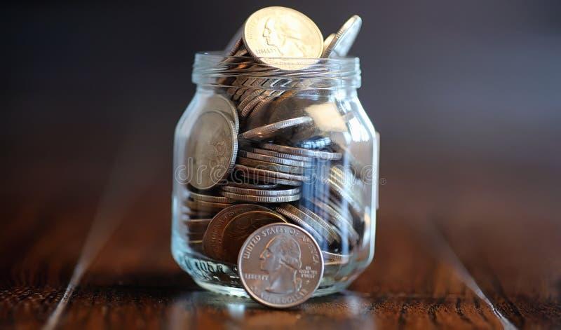 Mynt i en glass krus på ett trägolv Fick- besparingar från mynt fotografering för bildbyråer