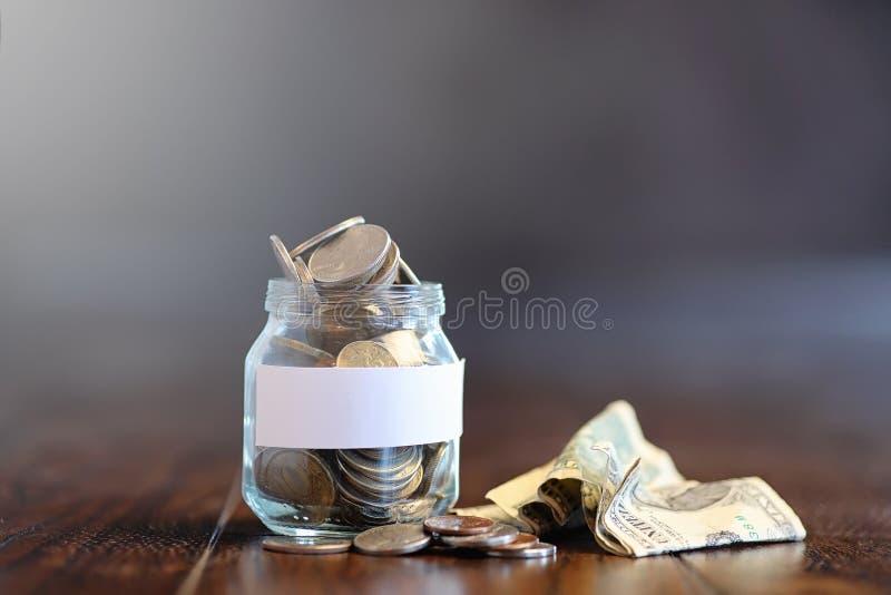 Mynt i en glass krus på ett trägolv Fick- besparingar från mynt royaltyfri fotografi