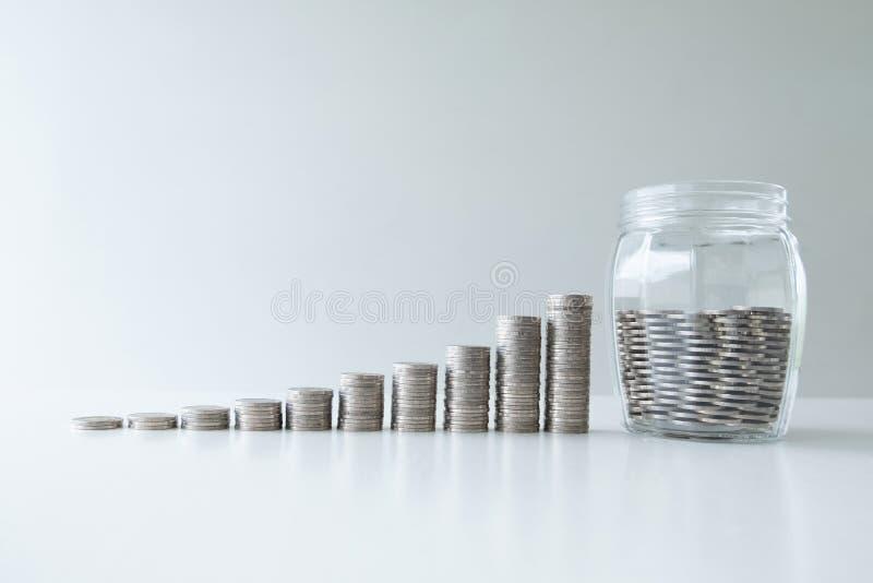 Mynt i glasflaskabanken med grafen för myntstångtillväxt, moment upp start upp affär till framgång, sparande pengar för framtida  arkivbilder