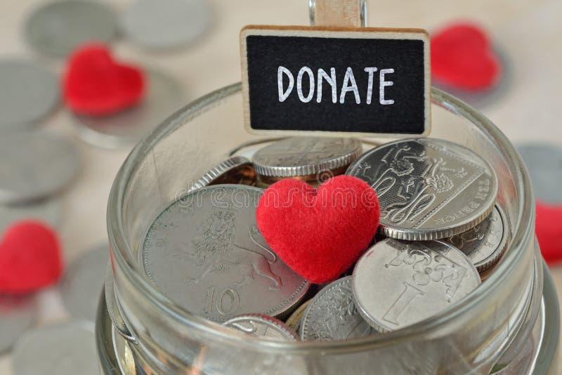 Mynt och hjärta i exponeringsglaspengarkrus med donerar etiketten - välgörenhetbegrepp arkivbilder