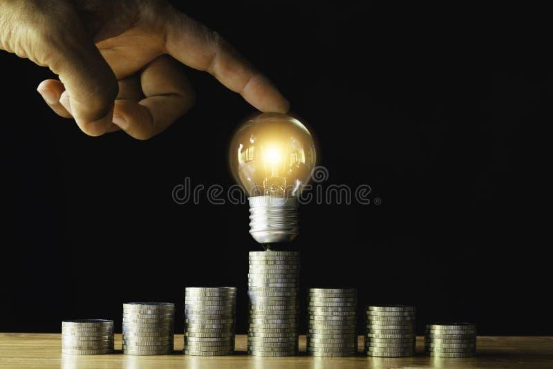 Mynt och ljus kula med handen som sätter till belysningen på trä för sparande pengar, energibegrepp i mörk bakgrund royaltyfri fotografi