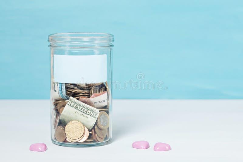Mynt och sedlar i exponeringsglaspengarkrus, finansiella donationer, välgörenhetbegrepp arkivbild