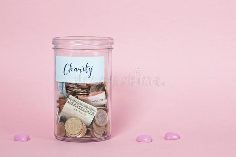 Mynt och sedlar i exponeringsglaspengarkrus, finansiella donationer, välgörenhetbegrepp royaltyfri bild