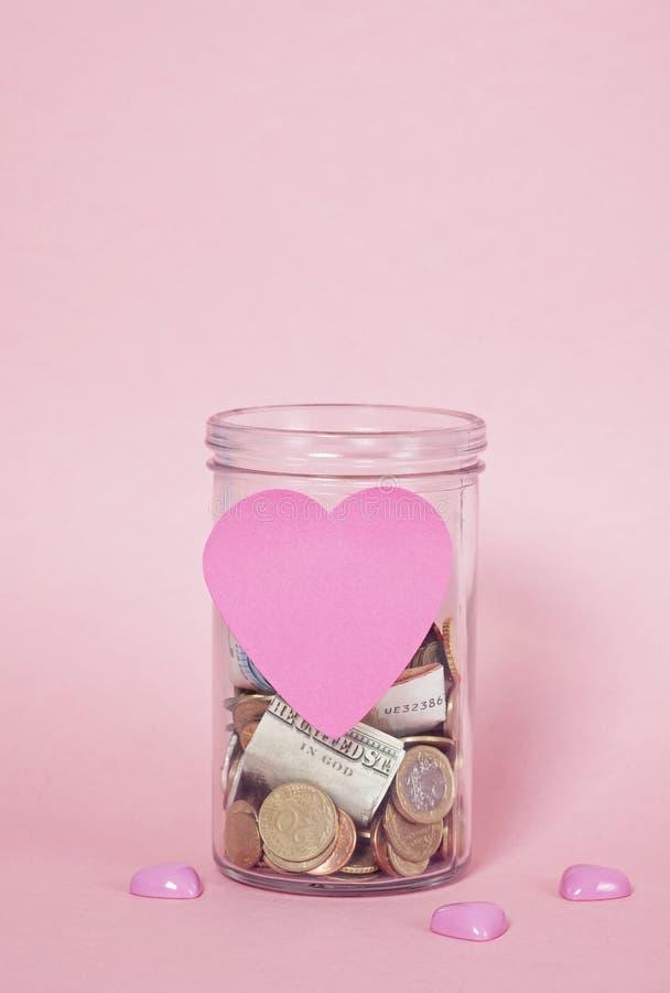 Mynt och sedlar i exponeringsglaspengarkrus, finansiella donationer, välgörenhetbegrepp arkivfoto