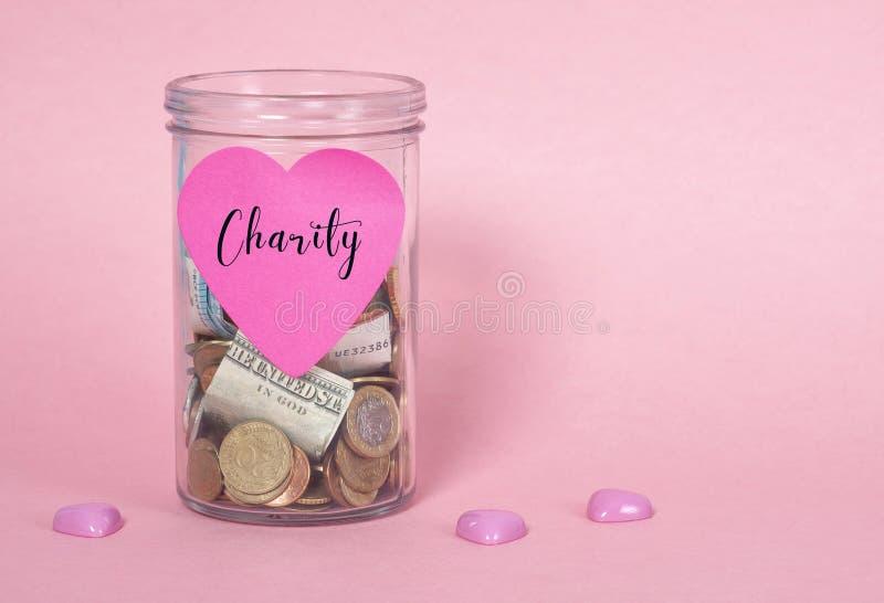 Mynt och sedlar i exponeringsglaspengarkrus, finansiella donationer, välgörenhetbegrepp fotografering för bildbyråer
