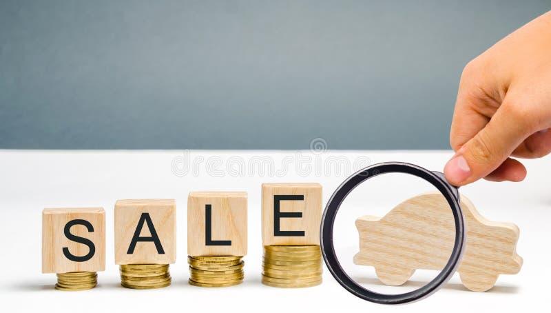 Mynt och tr?kvarter med ordet Sale och en miniatyrbil r sparande Att att k?pa en bil arkivbilder
