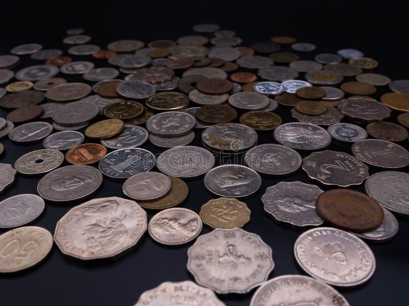 Mynt olika valutor på svart bakgrund arkivfoton