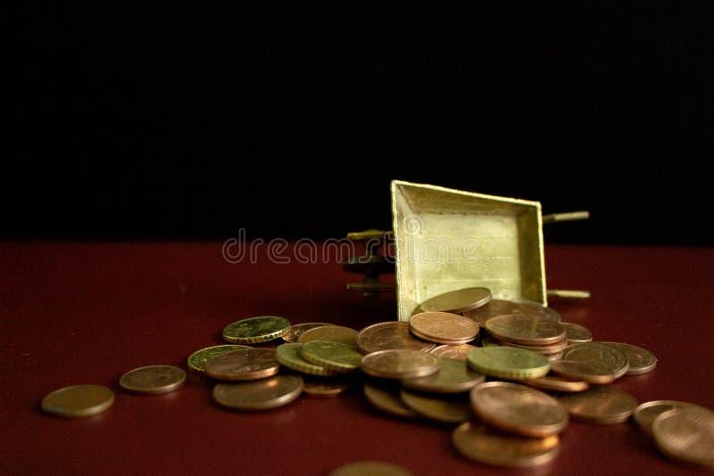 Mynt som faller från en guld- tappningskottkärra royaltyfri bild