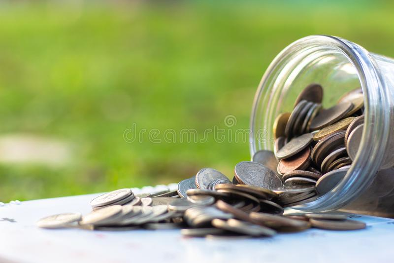 Mynt som spiller från en glass krus för pengar royaltyfri bild