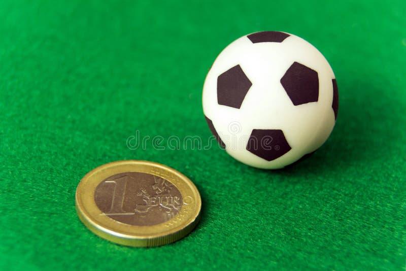 Mynta ett euro och en souvenirfotbollboll på en grön bakgrund Begreppspengar och sportar som slå vad på fotboll, korruption och,  royaltyfria bilder