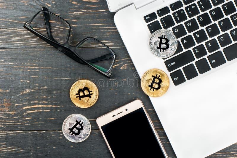 Myntar bitcoin med bärbara datorn royaltyfria bilder