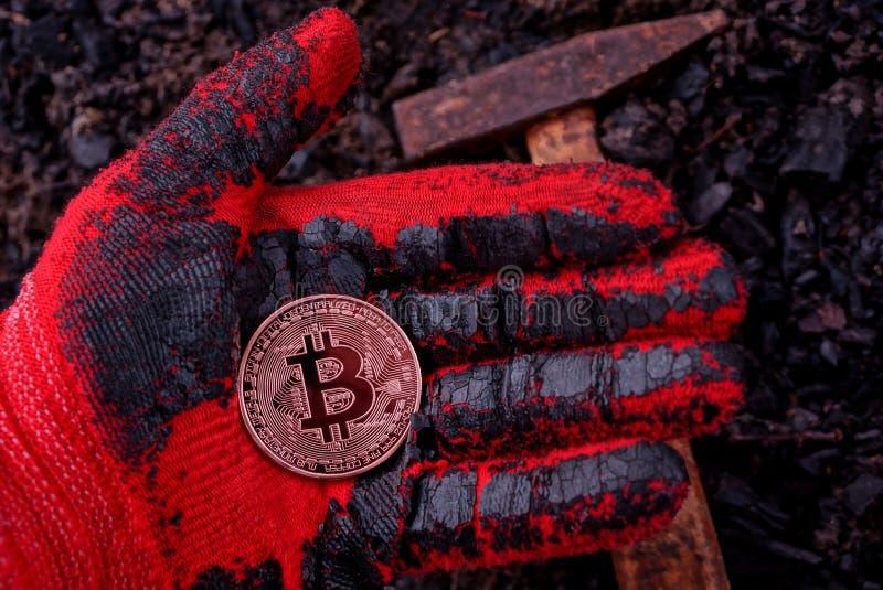 Myntbitcoin ligger på en behandskad hand mot jordningen och en hammare arkivfoton