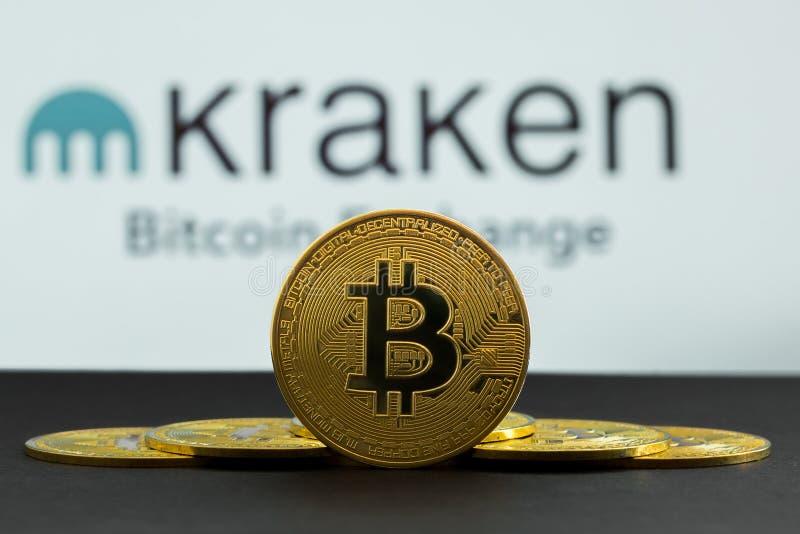 Mynten av bitcoin är framme av logo av Kraken crypto börsbakgrund I förgrunden är mynt för en BTC och på royaltyfria foton
