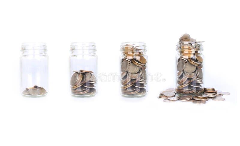 Myntpengar i glasflaskamoment från tomt till mycket, begrepp sav arkivfoto