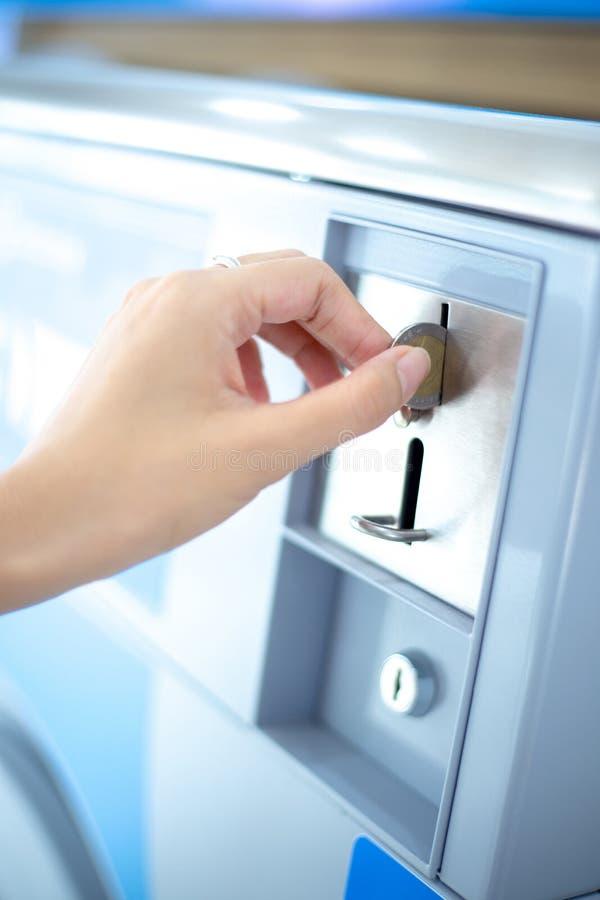 Myntspringa av mynttvätterivaruautomaten, mynt som sätter in vid handen arkivbild
