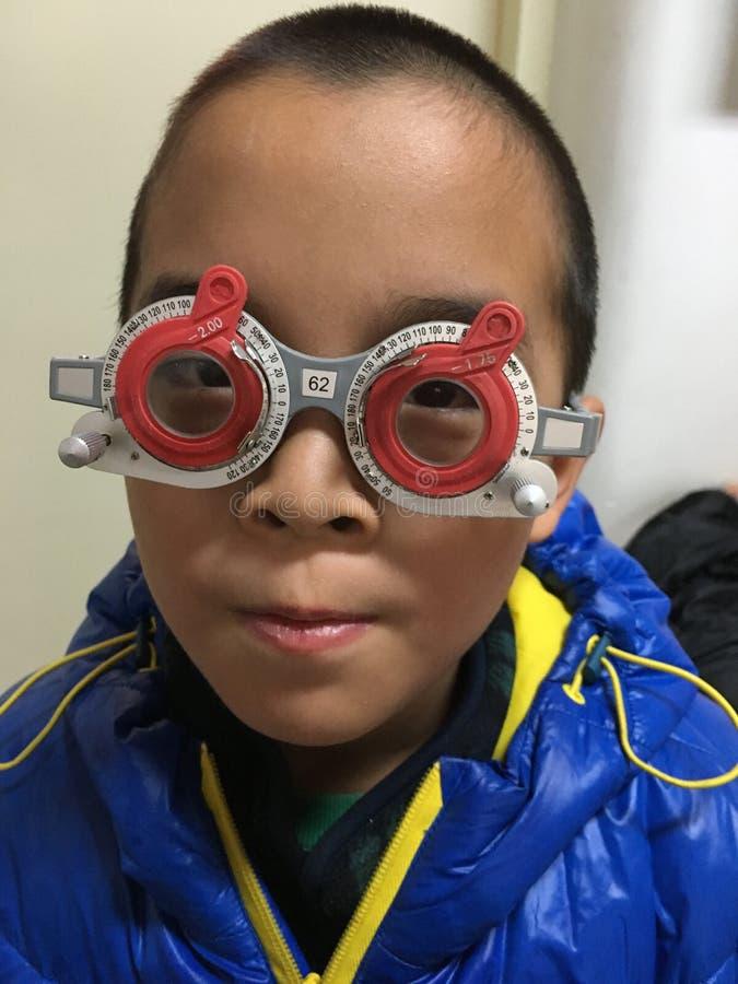 Myopia check. Little boy under eye check, youth myopia problem stock photography