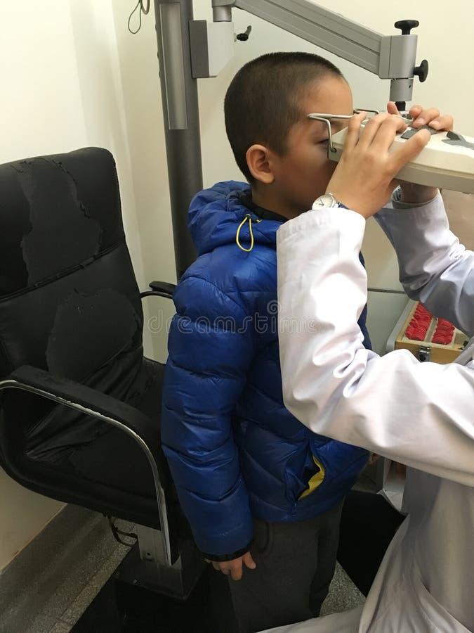 Myopia check. Little boy under eye check, youth myopia problem stock images