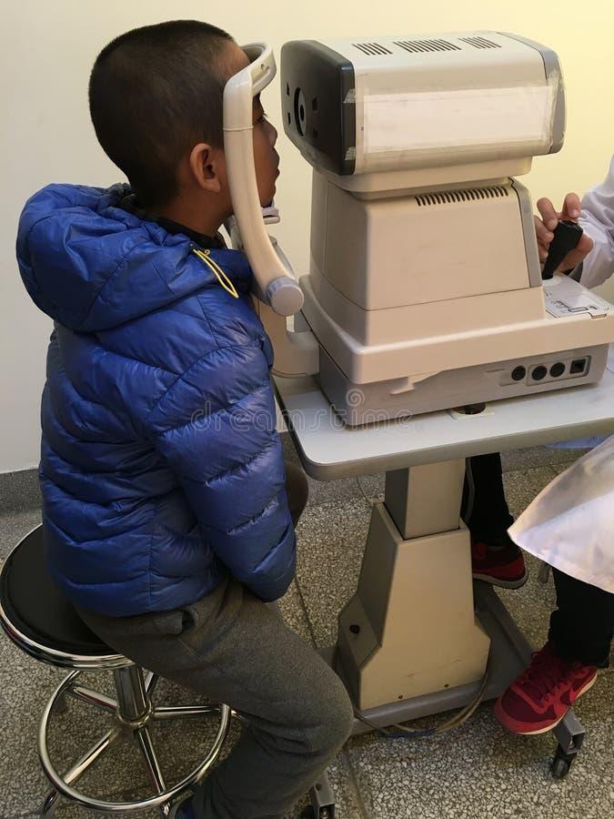 Myopia check. Little boy under eye check, youth myopia problem royalty free stock photo