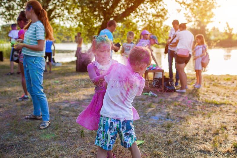 Myrhorod, Ucrania - 16 de junio de 2019: Dos niños que lanzan las pinturas en el festival de Holi del indio de colores fotos de archivo