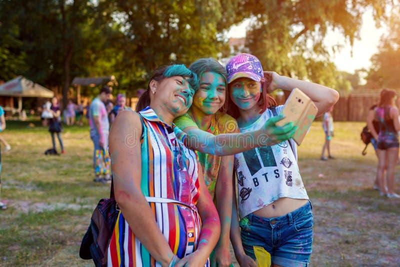 Myrhorod, Ucrania - 16 de junio de 2019: Familia que toma el selfie después de lanzar las pinturas en el festival de Holi del ind foto de archivo