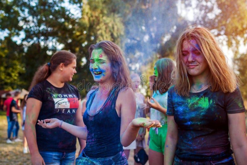 Myrhorod, Ucrania - 16 de junio de 2019: Grupo de amigos jovenes que lanzan las pinturas en el festival de Holi del indio de colo fotos de archivo