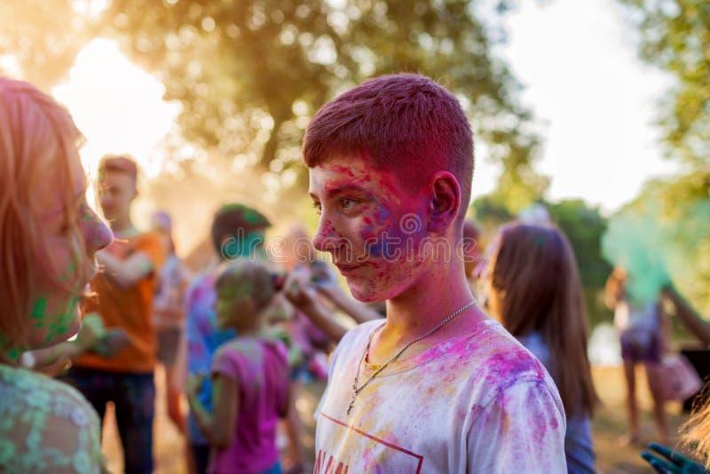 Myrhorod, Ucrania - 16 de junio de 2019: Grupo de amigos jovenes que lanzan las pinturas en el festival de Holi del indio de colo imagen de archivo libre de regalías