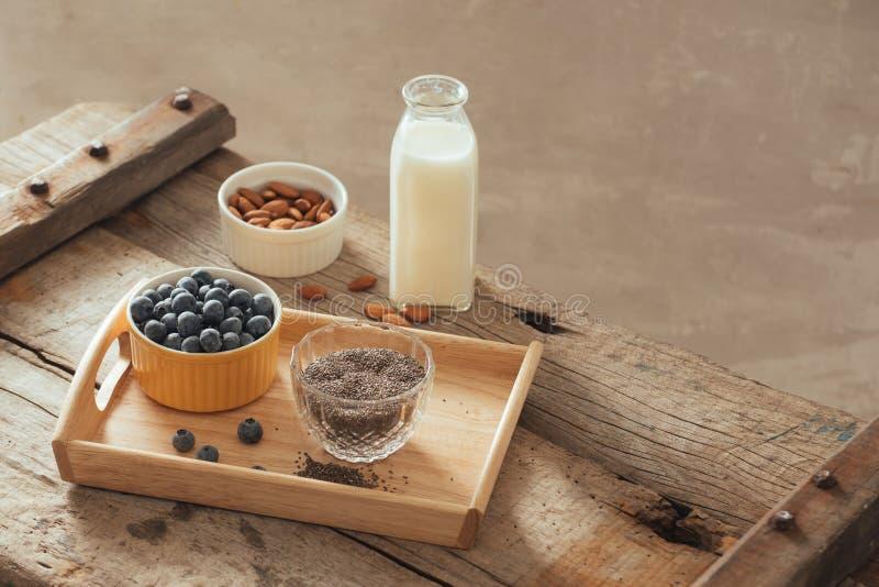 Myrtilles, amande et graines fraîches de chia avec du lait sur le conseil en bois Concept sain idéal de petit déjeuner photos stock