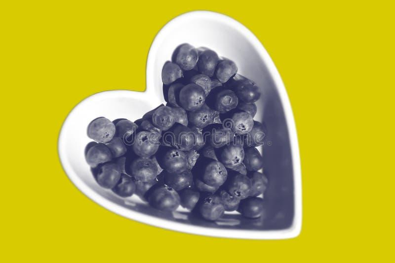Myrtilles dans la cuvette en forme de coeur images libres de droits