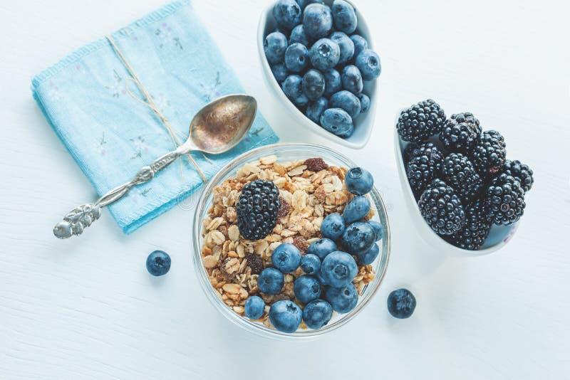 Myrtilles et mûres mûres sur le fond blanc dans des cuvettes en céramique blanches avec la granola Fin saine de petit déjeuner de image libre de droits