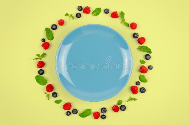 Myrtilles fraîches, framboises et feuille en bon état sur la vue supérieure avec le plat bleu et fond jaune en pastel de couleur  photo stock