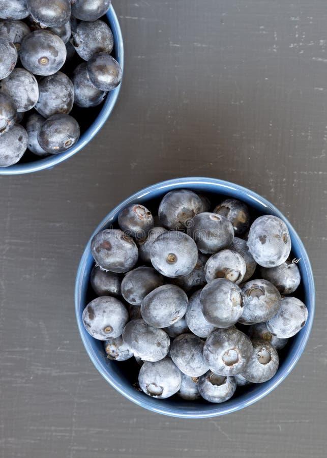 Myrtilles organiques mûres dans des cuvettes bleues sur un fond noir, vue supérieure Baie d'?t? Configuration plate, a?rienne, d' photos stock