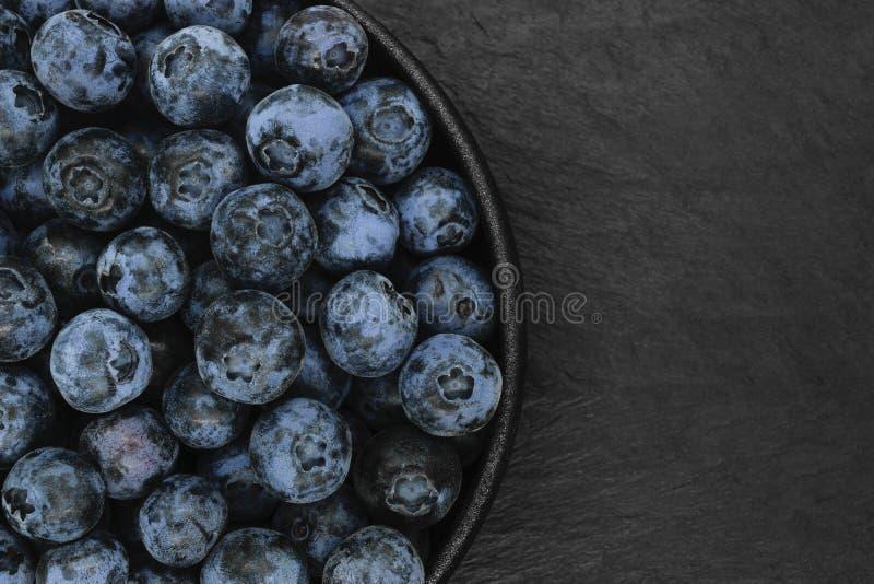 Myrtilles sur le fond en pierre noir photos stock