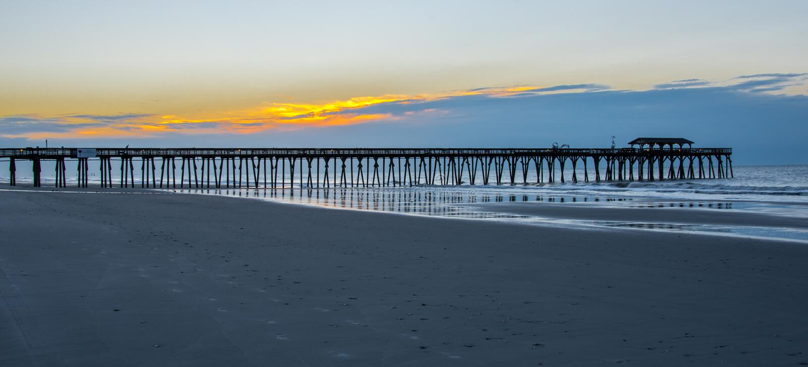 The Myrtle Beach, SC fishing pier in the sunrise stock photo