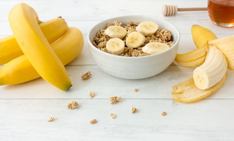 Mysli med Granola och nya bananer fotografering för bildbyråer
