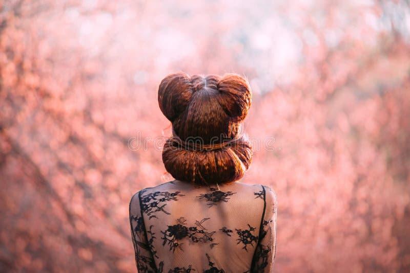 Mysteri?se Dame, wenn ein kreativer Frisurstift-oben, von der R?ckseite schie?t, ohne ein Gesicht Rotes Haar verdrehte kreativ si lizenzfreie stockfotos