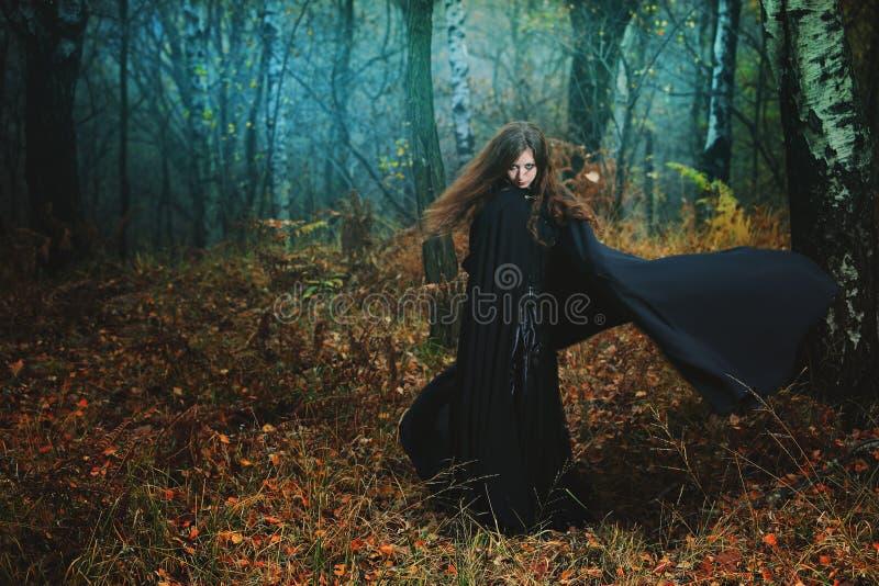 Mysteriöse Frau, die in magischen Wald geht lizenzfreie stockfotos