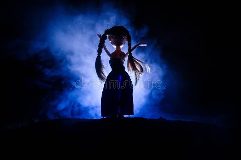 Mysteriöse Frau, Horrorszene der furchtsamen Geistpuppenfrau auf dunkelblauem Hintergrund mit Rauche lizenzfreies stockbild