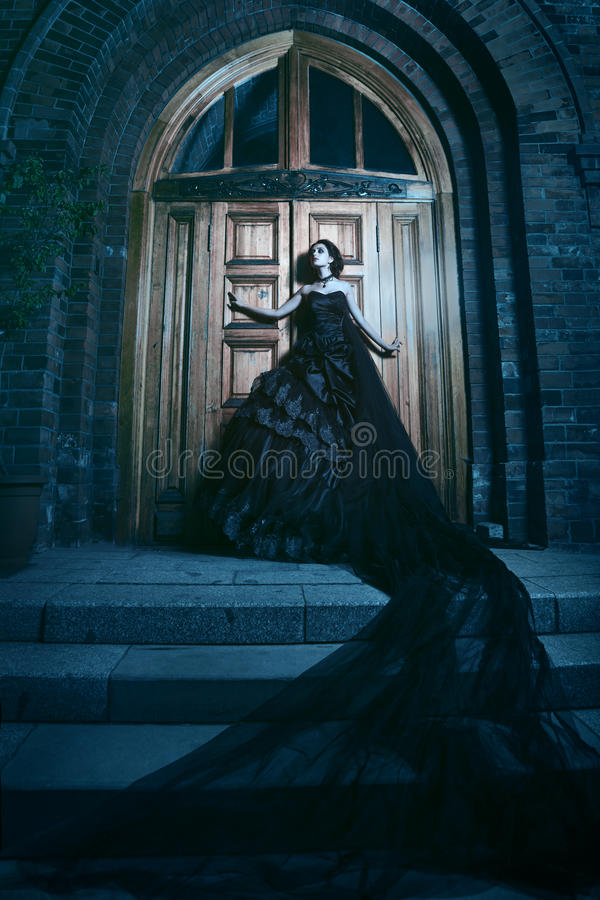 Mysteriöse Frau im schwarzen Kleid nahe Kirche lizenzfreie stockfotos