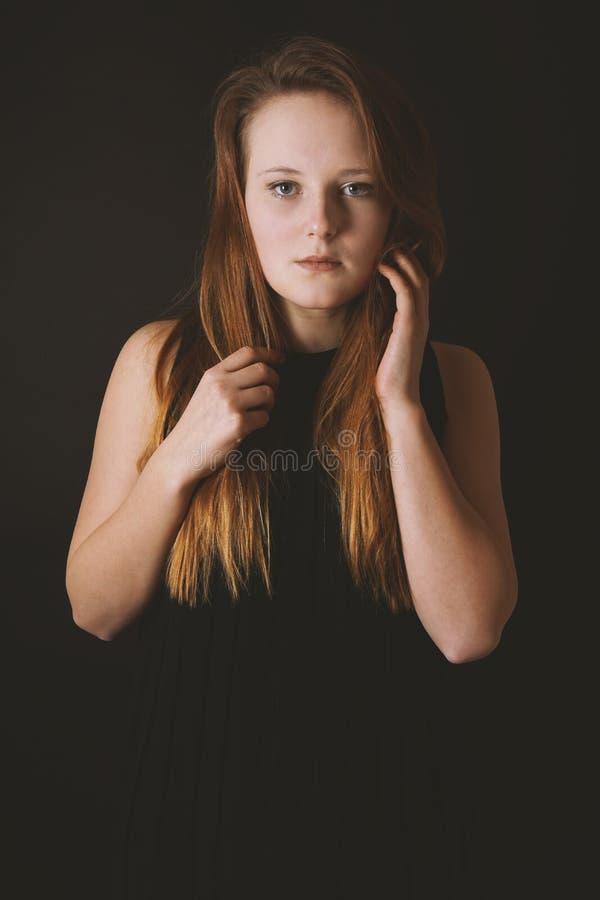 Mysteriöse junge Dame, die schwarzes Kleid auf schwarzem Hintergrund trägt stockbild