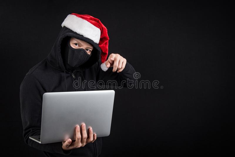 Mysteriöser männlicher Sankt-Hacker, der Laptop-Computer hält lizenzfreies stockfoto