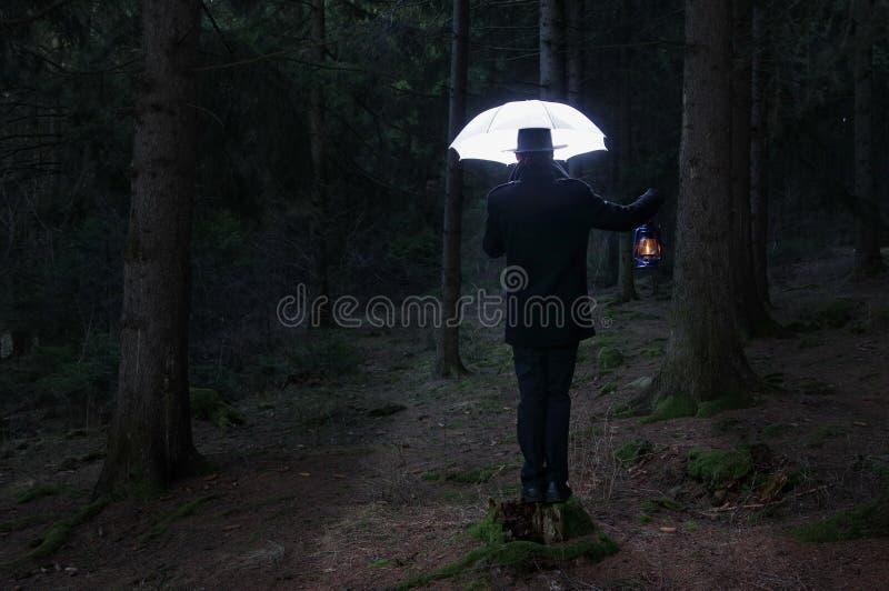 Mysteriöser Mann und der Beleuchtungsregenschirm lizenzfreies stockbild