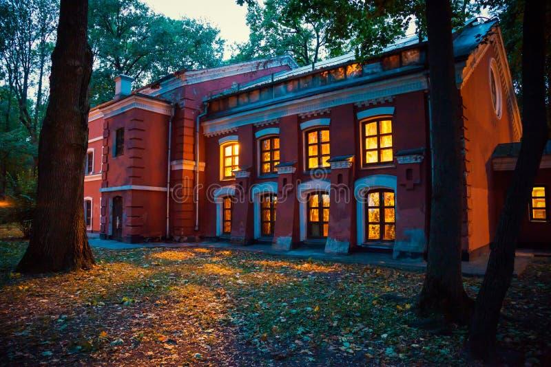 Mysteriöses Halloween-Haus mit gelbem Licht von Fenster spät a stockbilder