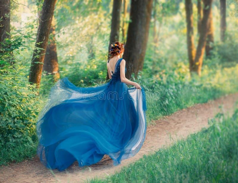 Mysteri?ses M?dchen mit dem roten umsponnenen Haar l?uft vom k?niglichen Feiertag, Dame im langen eleganten blauen Kleid mit Flie lizenzfreies stockbild
