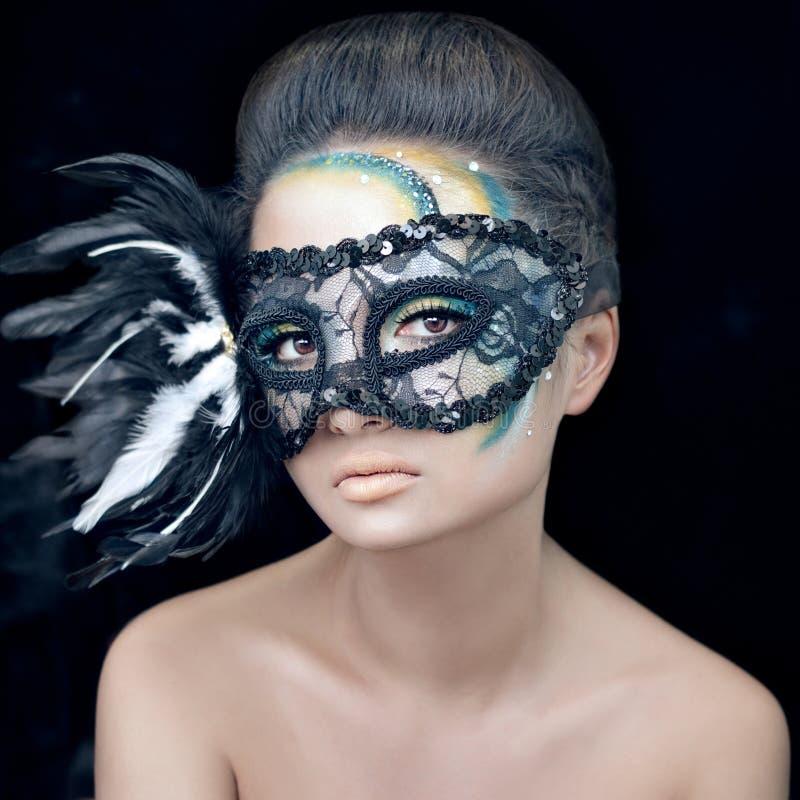 Mysteriöses schönes Mädchen in einer schwarzen Maske mit Federn mit grünem kreativem Make-up im Studio auf einem dunklen Hintergr stockfotos